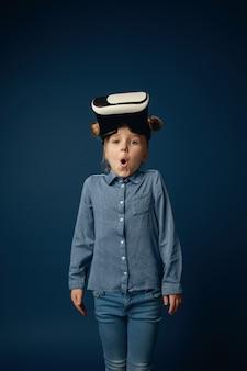 Маленькая девочка в джинсах и рубашке с очками гарнитуры виртуальной реальности