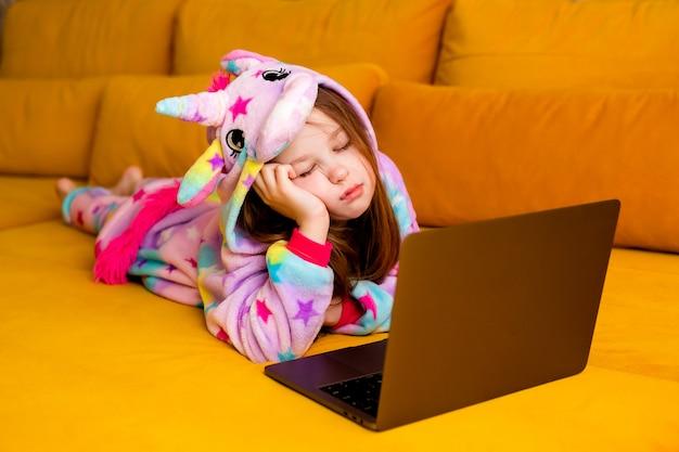 Маленькая девочка в кигуруми лежит дома на диване