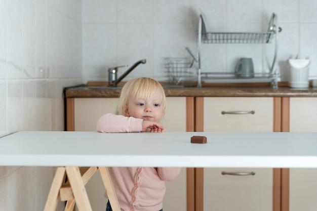 부엌에서 어린 소녀는 테이블에 사탕에 도달합니다. 금단의 과자.