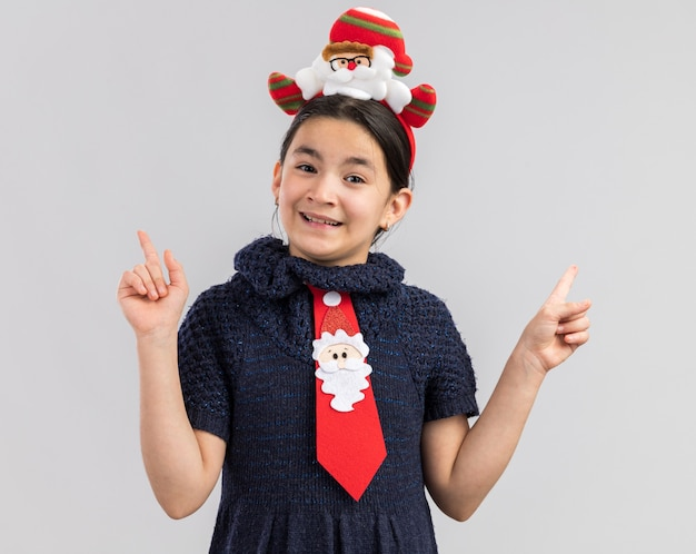 人差し指を示す幸せで前向きな笑顔の頭に面白いクリスマスの縁と赤いネクタイを着ているニットドレスの少女