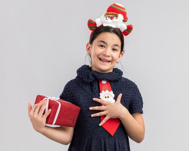 Маленькая девочка в вязаном платье в красном галстуке с забавным рождественским ободком на голове держит рождественский подарок, весело улыбается и чувствует благодарность