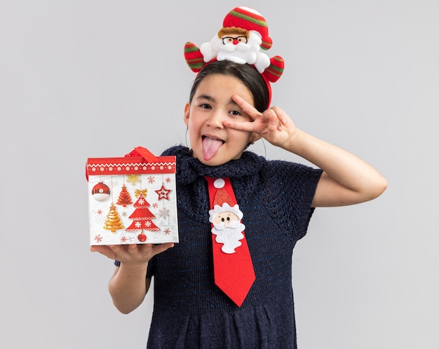 赤いネクタイを身に着けているニットドレスの少女が頭に面白いクリスマスの縁を持ってクリスマスプレゼントを持って舌を突き出してvサインを見せて幸せで楽しい