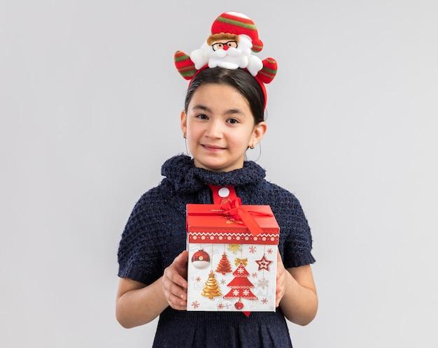 幸せで前向きな顔に笑顔で見てクリスマスの贈り物を保持している頭に面白いクリスマスの縁と赤いネクタイを着ているニットドレスの少女