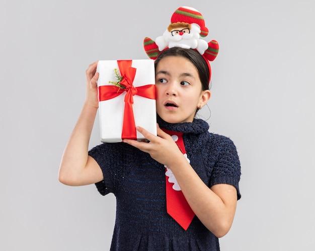 赤いネクタイを身に着けているニットドレスの少女が頭に面白いクリスマスの縁を持ってクリスマスプレゼントを脇に見て驚いた