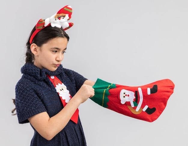 Маленькая девочка в вязаном платье в красном галстуке с забавным рождественским ободком на голове держит рождественский чулок, выглядит заинтригованным