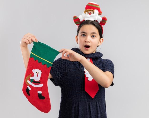 Маленькая девочка в вязаном платье в красном галстуке с забавным рождественским ободком на голове держит рождественский чулок с удивленным видом