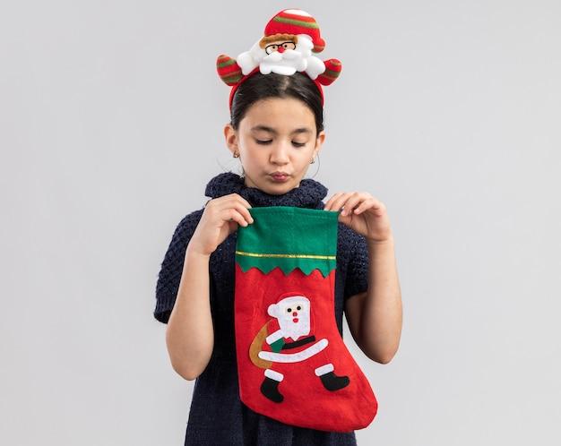 ニットのドレスを着た少女が赤いネクタイを着て、頭に面白いクリスマスの縁があり、クリスマスの靴下を開いて興味をそそられています