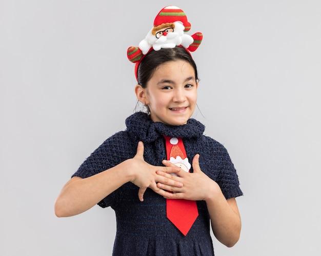 胸に手をつないで頭に面白いクリスマスの縁と赤いネクタイを着ているニットドレスの少女は感謝を感じています