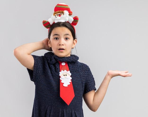 赤いネクタイを身に着けているニットドレスの少女は、腕の外で混乱しているように見える頭に面白いクリスマスの縁があります