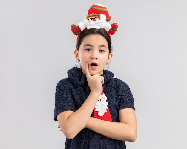 驚いて驚いたように見える頭に面白いクリスマスの縁と赤いネクタイを着ているニットドレスの少女