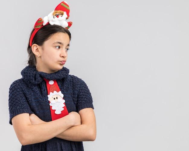 腕を組んで不機嫌そうに見ている頭に面白いクリスマスの縁と赤いネクタイを着ているニットドレスの少女