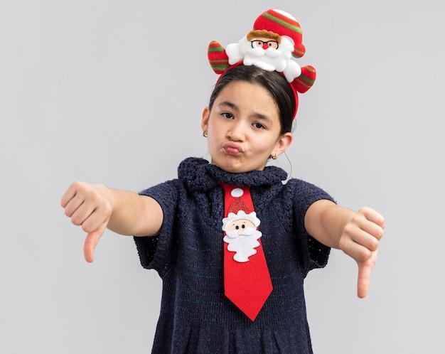 頭に面白いクリスマスの縁と赤いネクタイを着てニットドレスの少女
