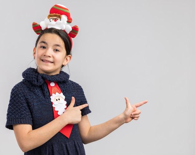 頭に面白いクリスマスの縁と赤いネクタイを身に着けているニットドレスの少女は、人差し指を横に向けて幸せで前向きに見えます