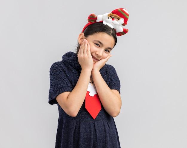 幸せで前向きな笑顔に見える頭に面白いクリスマスの縁と赤いネクタイを着てニットドレスの少女