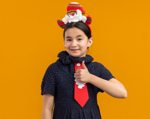 Маленькая девочка в вязаном платье с красным галстуком и забавным рождественским ободком на голове выглядит счастливой и грустно показывает палец вверх