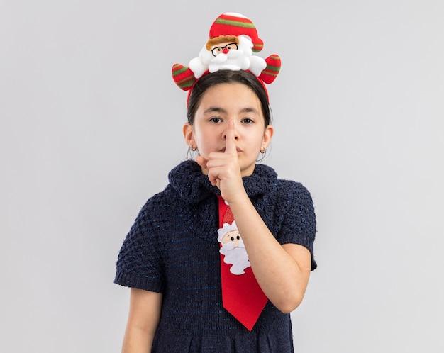 頭に面白いクリスマスの縁と赤いネクタイを着て、唇に指で沈黙のジェスチャーをしているニットドレスの少女