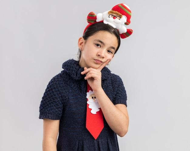 困惑しているように見える頭に面白いクリスマスの縁と赤いネクタイを着ているニットドレスの少女
