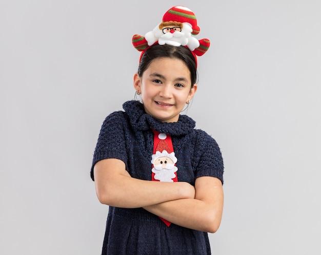 腕を組んで自信を持って笑顔に見える頭に面白いクリスマスの縁と赤いネクタイを着ているニットドレスの少女