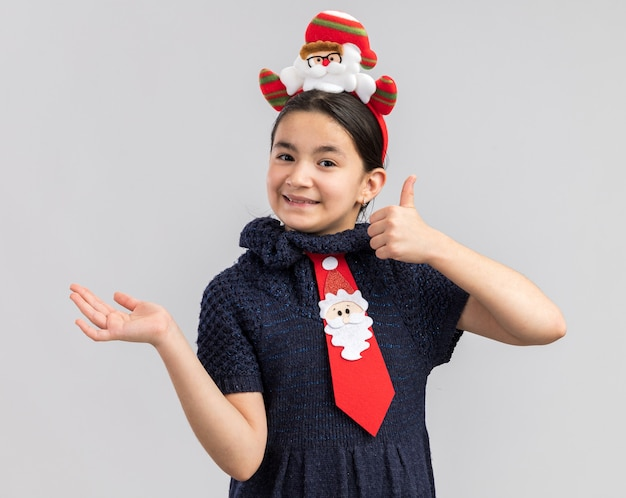 赤いネクタイを身に着けているニットドレスの少女が頭に面白いクリスマスの縁を持って笑顔を見せて親指を立ててコピースペースを手の腕で提示