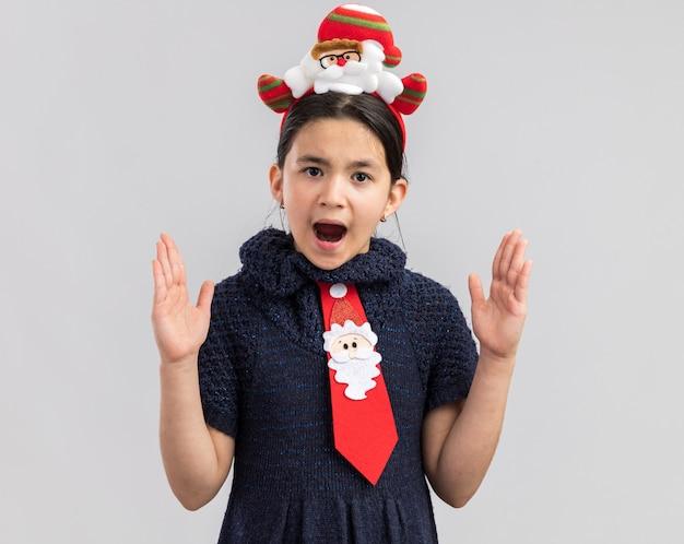 頭に面白いクリスマスの縁と赤いネクタイを着ているニットドレスの少女は、手で大きなサイズのジェスチャーを作って驚いて見えます