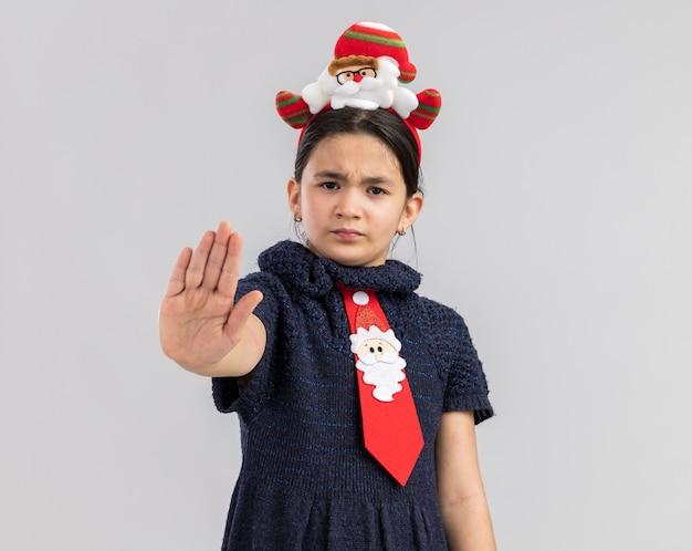 頭に面白いクリスマスの縁と赤いネクタイを着て真面目な顔で見て停止ジェスチャーを持っていたニットドレスの少女