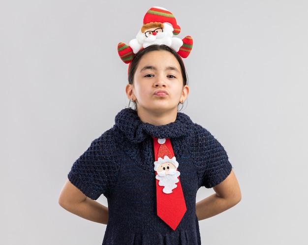 スマートな顔に笑顔で見て頭に面白いクリスマスの縁と赤いネクタイを着てニットドレスの少女