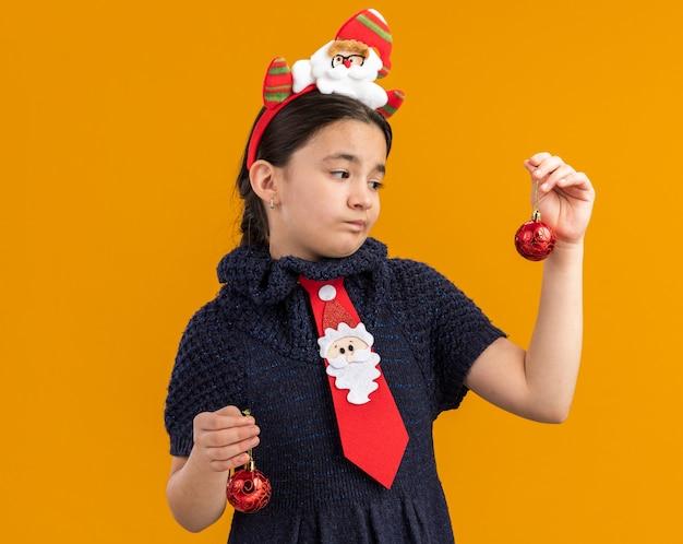 Маленькая девочка в вязаном платье в красном галстуке с забавным ободком на голове держит елочные шары, выглядит смущенным и сомневающимся