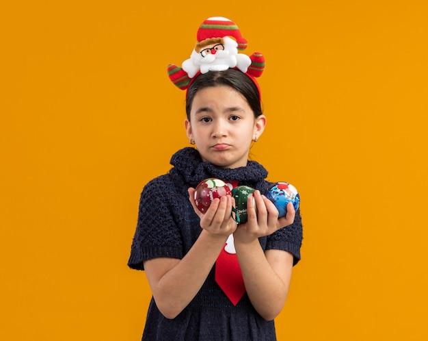 슬픈 표정으로 찾고 크리스마스 공을 들고 머리에 재미있는 테두리와 빨간 넥타이를 입고 니트 드레스에 어린 소녀