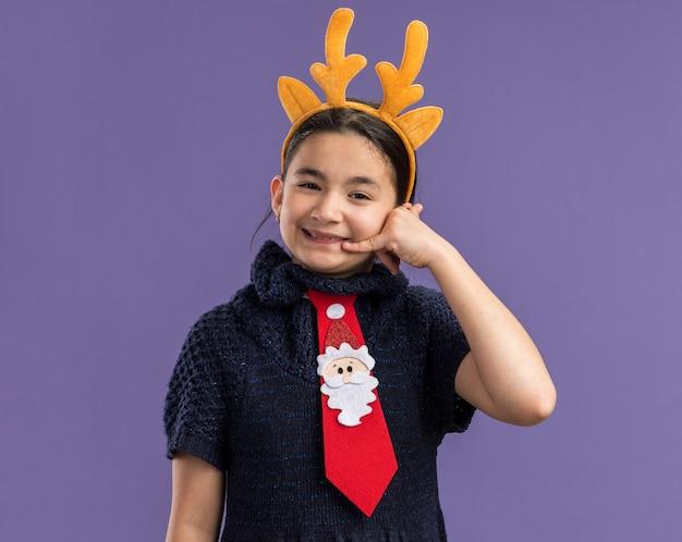 Маленькая девочка в вязаном платье в красном галстуке с забавным ободком с оленьими рогами на голове счастлива и позитивна, делая жест, называя меня улыбающимся, стоя над фиолетовой стеной