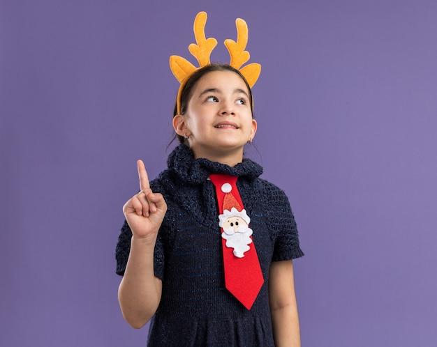 紫色の壁の上に立っている新しいアイデアを持っている人差し指を示す驚いた顔に笑顔で見上げる頭に鹿の角を持つ面白い縁と赤いネクタイを身に着けているニットドレスの少女