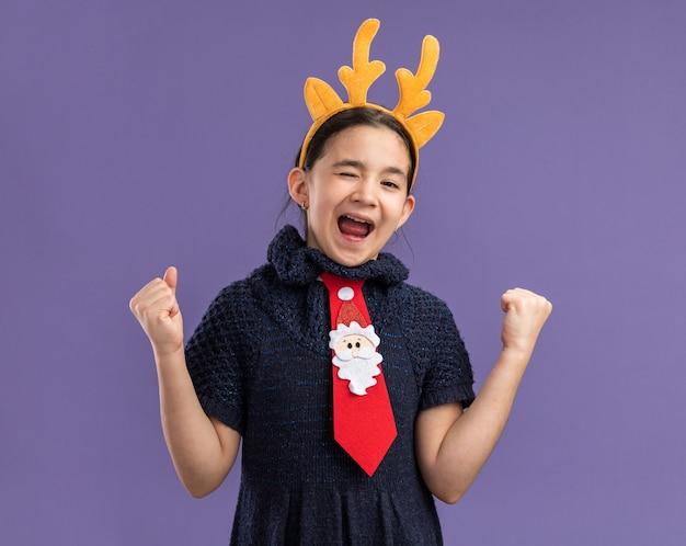 Маленькая девочка в вязаном платье в красном галстуке с забавным ободком с оленьими рогами на голове кричит от счастья и возбуждения, сжимая кулаки, стоя над фиолетовой стеной