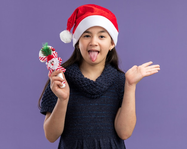 Маленькая девочка в вязаном платье в шапке санта-клауса держит рождественскую конфету, счастливая и радостная, высунув язык, стоя над фиолетовой стеной