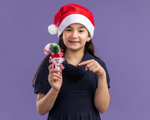 크리스마스 사탕 지팡이에 검지 손가락으로 가리키는 산타 모자를 쓰고 니트 드레스에 어린 소녀 행복하고 긍정적 인 보라색 벽 위에 유쾌하게 서 웃고
