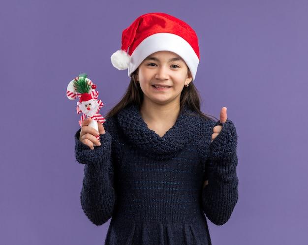 보라색 벽 위에 유쾌하게 서있는 크리스마스 사탕 지팡이를 들고 산타 모자를 쓰고 니트 드레스에 어린 소녀