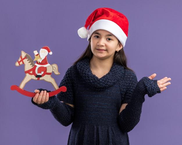 紫色の壁の上に立っている顔に笑顔でクリスマスのおもちゃを保持しているサンタの帽子をかぶったニットドレスの少女