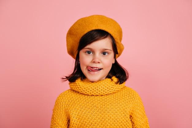 Маленькая девочка в вязаном свитере, стоящем на розовой стене. ребенок позирует с высунутым языком.