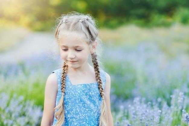 ラベンダー畑の少女。子供のファンタジー。夏の紫のラベンダー畑で花をスニッフィング笑顔の女の子。