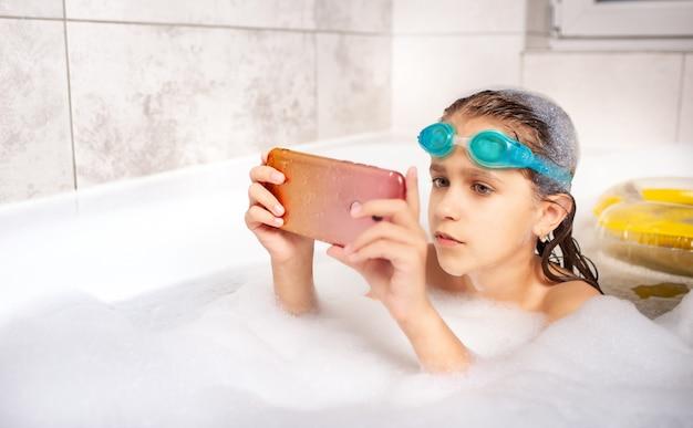 Маленькая девочка делает селфи с помощью смартфона, купаясь в пенной ванне дома