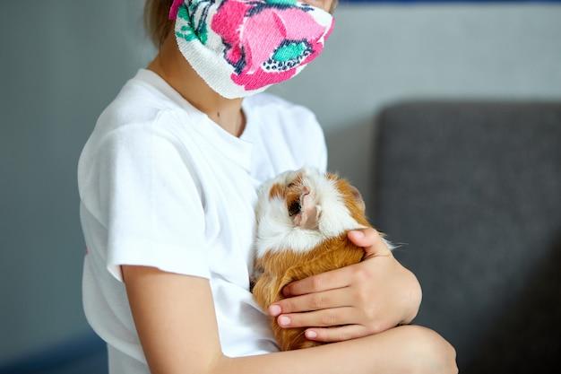 Маленькая девочка в маске играя с красной морской свинкой, cavy дома на софе пока в карантине.