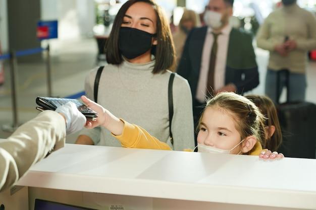 Маленькая девочка в маске вместе с матерью дает документы перед регистрацией в аэропорту