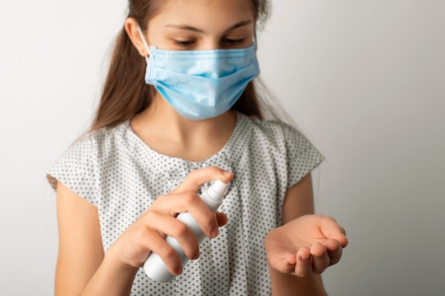 Маленькая девочка в медицинской маске, применяя антибактериальный гель