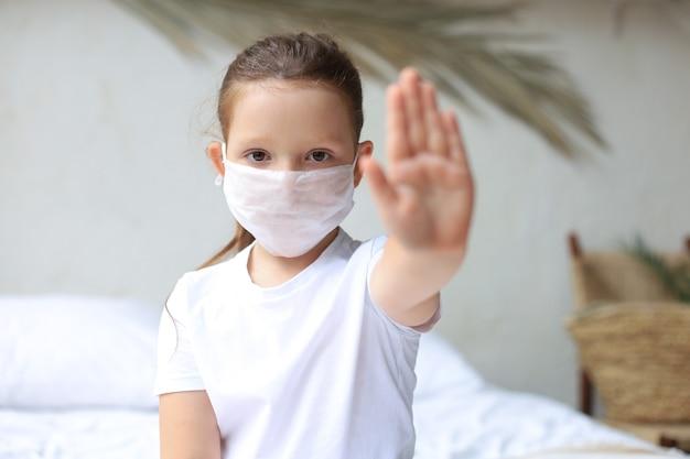 Covid-19の流行の停止を示す医療マスクの少女。