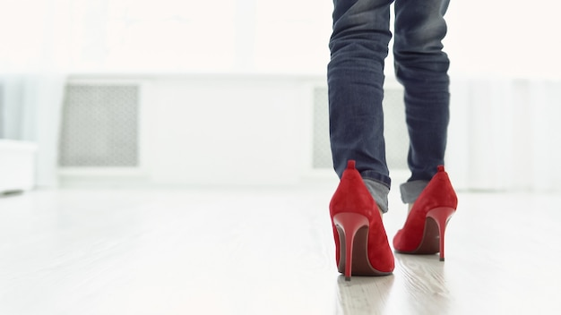 母の赤い靴を履いた少女が家の中を歩いています。背面図、コピースペース