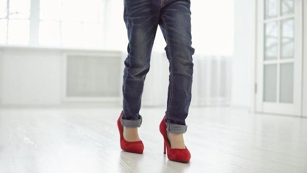 母の赤い靴を履いた少女が家の中を歩き回っています。