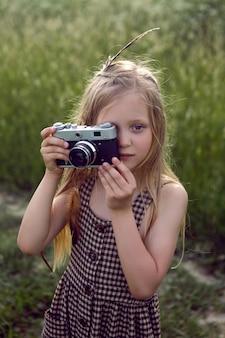 Маленькая девочка на природе с камерой