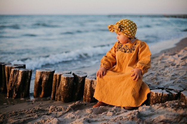 バルト海のビーチの防波堤に座っている東洋の服を着た少女