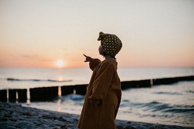 日没時にビーチに沿って歩く東洋の服を着た少女