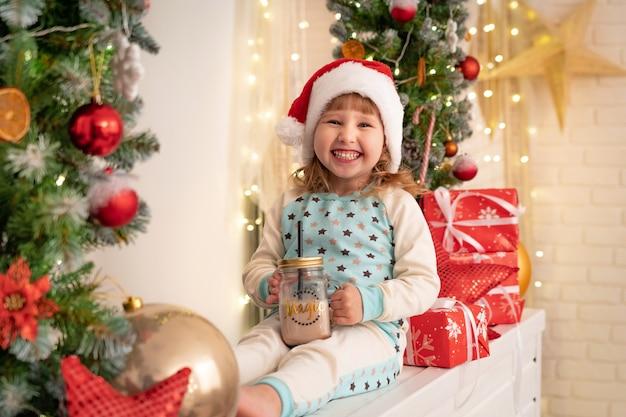 코코아 우유를 마시는 잠 옷과 산타 모자에 소녀
