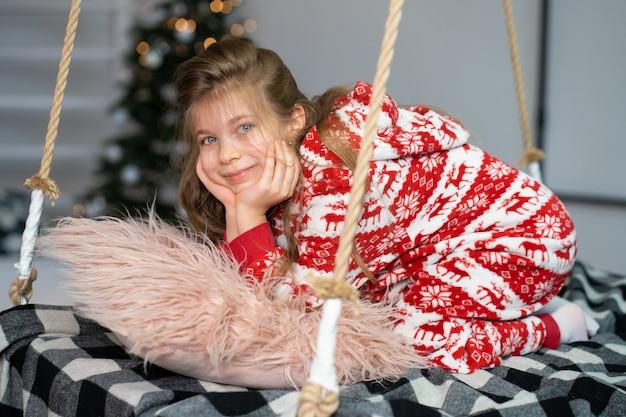 잠옷을 입은 어린 소녀는 축제 밤에 잠을 잘 수 없습니다.