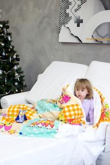 パジャマ姿の少女は、クリスマスツリーのある部屋の毛布の下で遊んで隠れています
